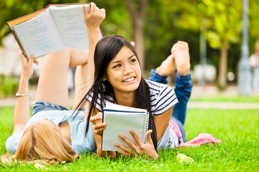 Teenage Girls Reading Books on Lawn
