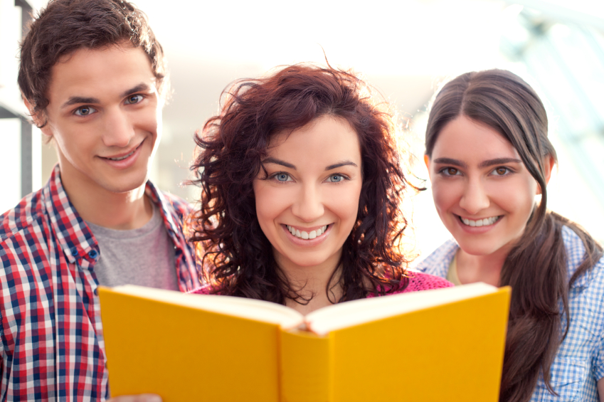 Mother holding a book with teenage children on either side